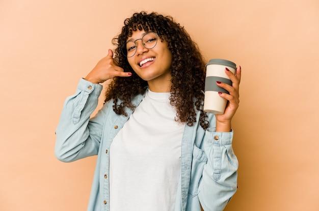 Junge afroamerikaner-afro-frau, die einen kaffee zum mitnehmen hält, der eine handy-anrufgeste mit den fingern zeigt.
