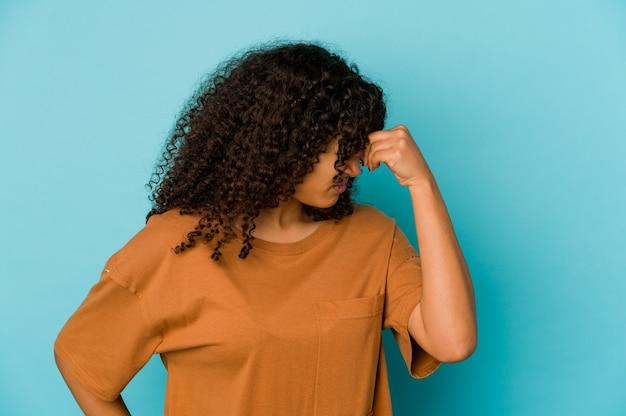 Junge afroamerikaner-afro-frau isoliert, die einen kopfschmerz hat, der vorderseite des gesichts berührt.