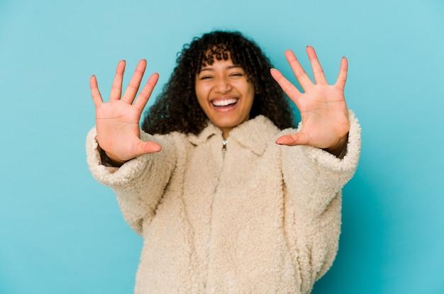 Junge afroamerikaner-afro-frau isoliert, nummer zehn mit den händen zeigend.