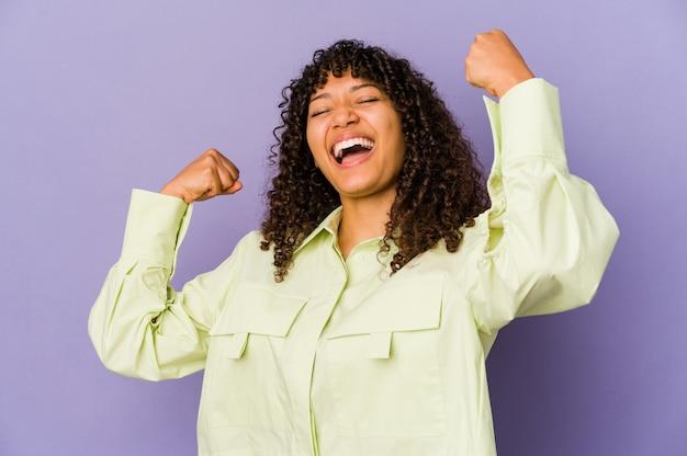 Junge afroamerikaner-afrofrau isolierte das erhöhen der faust nach einem sieg, gewinnerkonzept.