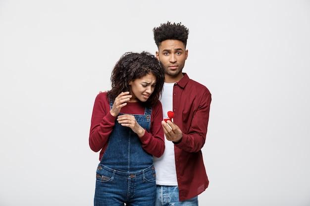 Junge afroamerikaner erschrockene freundin, die einen heiratantrag zurückweist