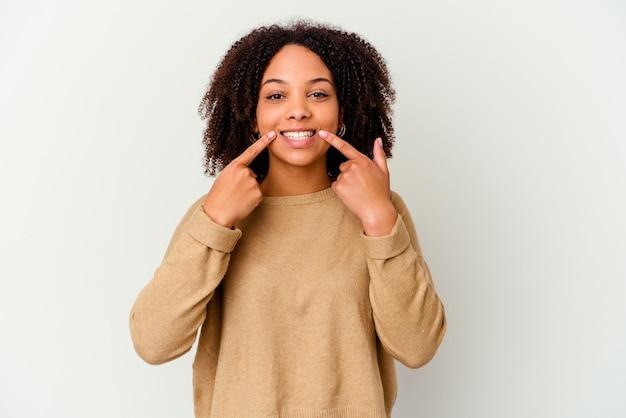 Junge afroamerikaner gemischte rasse frau isoliert lächelt und zeigt finger auf mund.