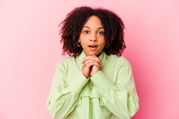 Junge afroamerikaner gemischte rassenfrau isoliert betend für glück, erstaunt und mundöffnung schauend nach vorne.