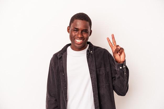 Junge afroamerikaner isoliert auf weißem hintergrund freudig und sorglos zeigt ein friedenssymbol mit den fingern.