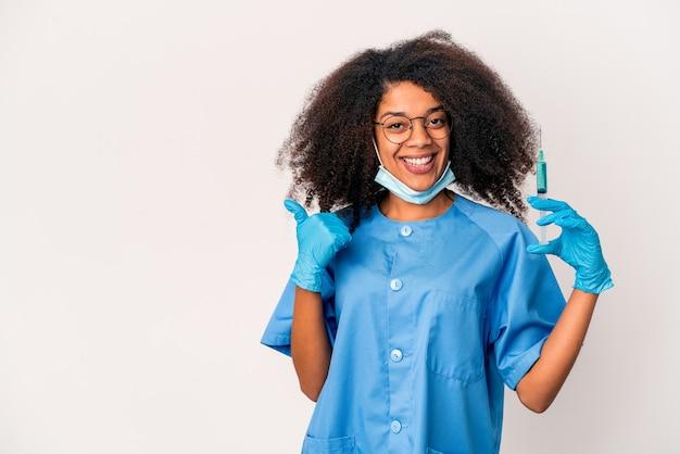 Junge afroamerikaner lockige ärztin, die eine spritze hält lächelnd und daumen hoch hält
