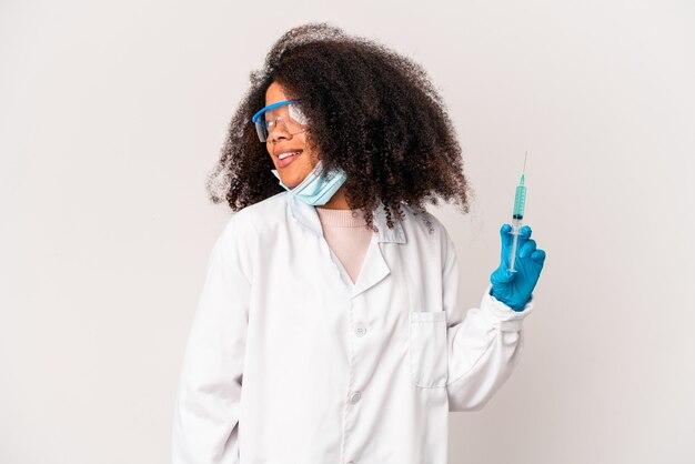 Junge afroamerikaner lockige ärztin, die eine spritze hält, schaut lächelnd, fröhlich und angenehm beiseite.