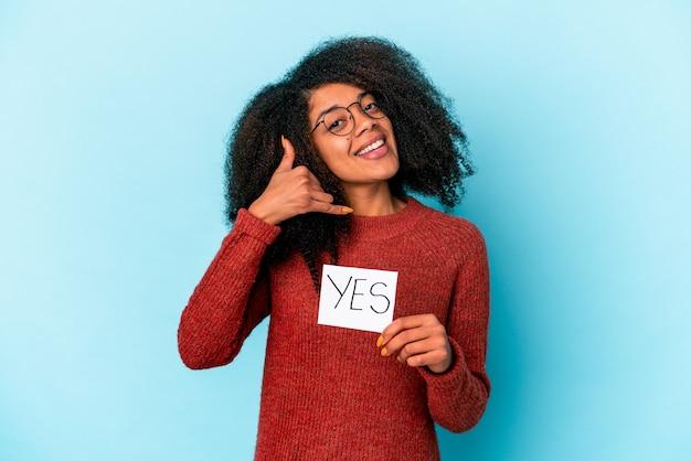 Junge afroamerikaner lockige frau, die ein ja-plakat hält, das eine handy-anrufgeste mit den fingern zeigt.