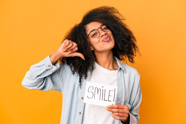 Junge afroamerikaner lockige frau, die ein lächelnbotschaftsplakat hält, fühlt sich stolz und selbstbewusst, beispiel zu folgen.