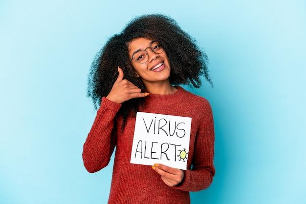 Junge afroamerikaner lockige frau, die ein virusalarmplakat hält, das eine handy-anrufgeste mit den fingern zeigt.