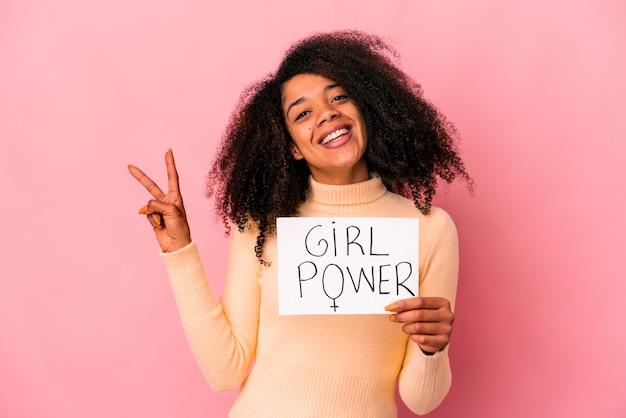 Junge afroamerikaner lockige frau, die eine mädchenpower-nachricht auf einem plakat freudig und sorglos hält, das ein friedenssymbol mit fingern zeigt.
