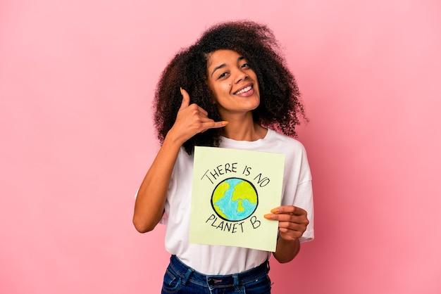 Junge afroamerikaner lockige frau, die eine planetennachricht auf einem plakat hält, das eine handy-anrufgeste mit den fingern zeigt.