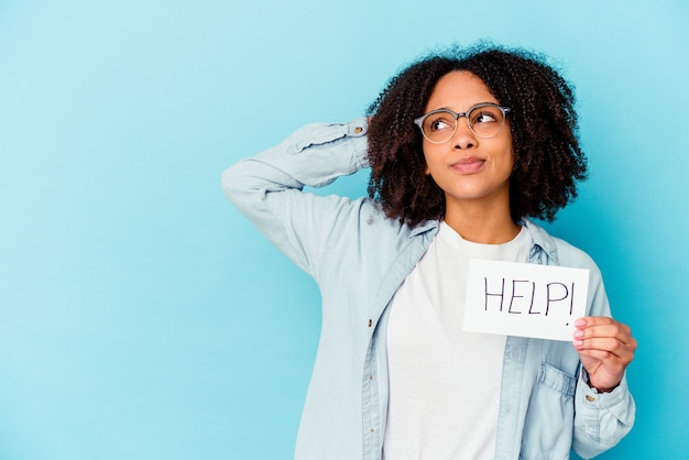 Junge afroamerikaner lockige frau, die einen karton mit einer nachricht hält