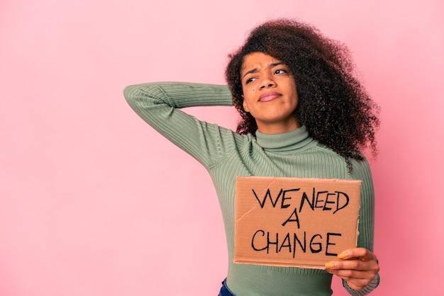 Junge afroamerikaner lockige frau halten eine wir brauchen einen wechselkarton, der den hinterkopf berührt, denkt und eine wahl trifft.