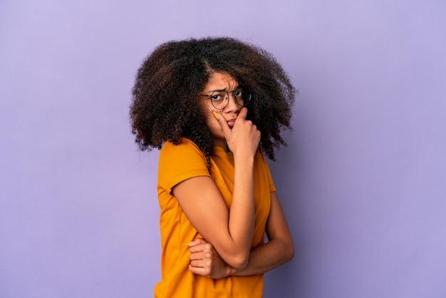 Junge afroamerikaner lockige frau isoliert auf lila wand ängstlich und ängstlich.