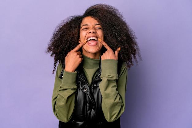 Junge afroamerikaner lockige frau lokalisiert auf lila hintergrund lächelt und zeigt finger auf mund.