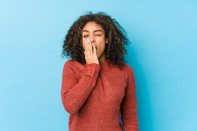 Junge afroamerikaner lockiges haar frau, die eine müde geste zeigt, die mund mit hand bedeckt.