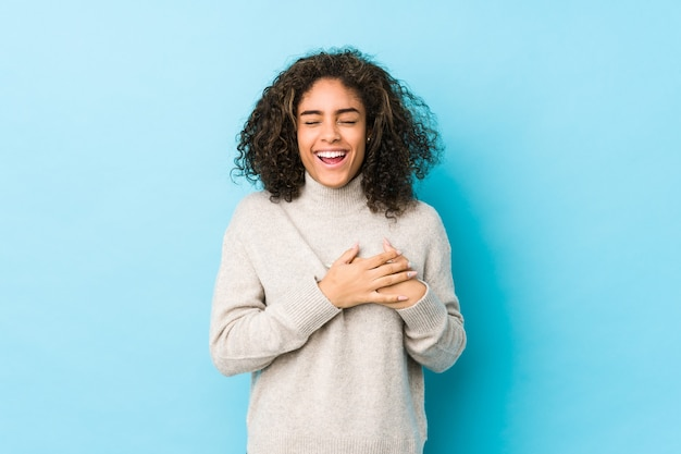Junge afroamerikaner lockiges haar frau lachend hände auf herz halten, konzept des glücks.