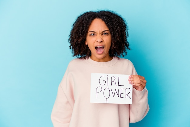 Junge afroamerikaner-mischrassenfrau, die ein frauenpower-konzept hält, das sehr wütend und aggressiv schreit.