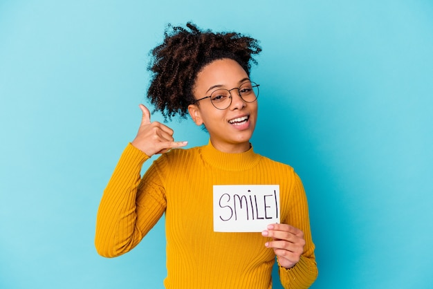 Junge afroamerikaner-mischrassenfrau, die ein lächelnkonzept hält, das eine handy-anrufgeste mit den fingern zeigt.