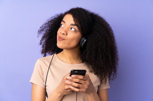 Junge afroamerikanerfrau auf lila wand, die musik mit einem handy und denken hört