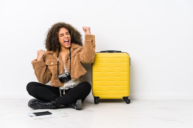 Junge afroamerikanerfrau bereit für eine reise, die faust nach einem sieg, gewinnerkonzept erhebt.