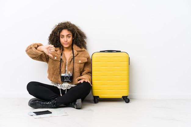 Junge afroamerikanerfrau bereit zu einer reise, die eine abneigungsgeste, daumen unten zeigt. uneinigkeit konzept.