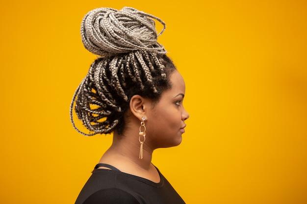 Junge afroamerikanerfrau der schönen seite mit dem angsthaar auf gelb