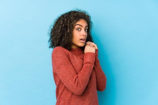 Junge afroamerikanerfrau des gelockten haares erschrocken und ängstlich.