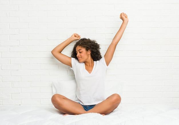 Junge afroamerikanerfrau, die auf dem bett sich ausdehnt
