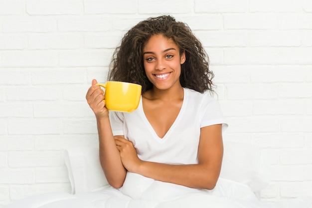 Junge afroamerikanerfrau, die auf dem bett sitzt und eine kaffeetasse hält, die zuversichtlich mit verschränkten armen lächelt.