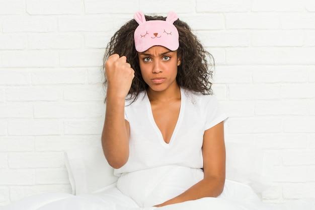 Junge afroamerikanerfrau, die auf dem bett sitzt und eine schlafmaske trägt, die faust zur kamera, aggressiven gesichtsausdruck zeigt.
