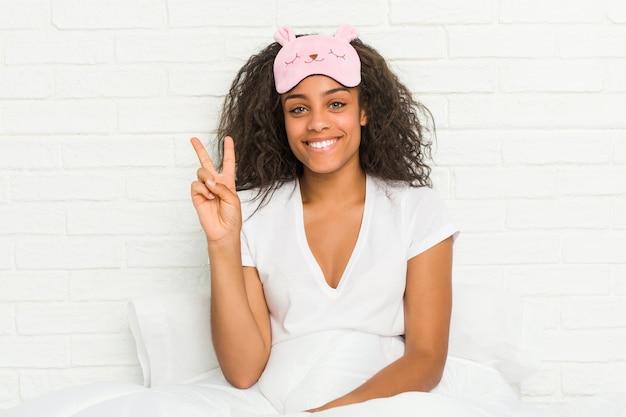 Junge afroamerikanerfrau, die auf dem bett sitzt und eine schlafmaske trägt, die nummer zwei mit den fingern zeigt.