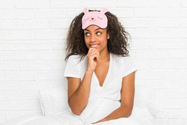 Junge afroamerikanerfrau, die auf dem bett sitzt und eine schlafmaske trägt, entspannte sich und dachte an etwas, das einen kopienraum betrachtete.