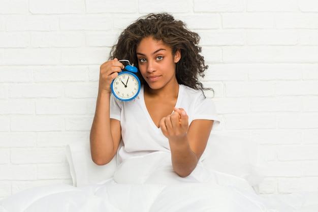 Junge afroamerikanerfrau, die auf dem bett sitzt und einen wecker hält, der mit finger auf sie zeigt, als ob die einladung näher kommt.