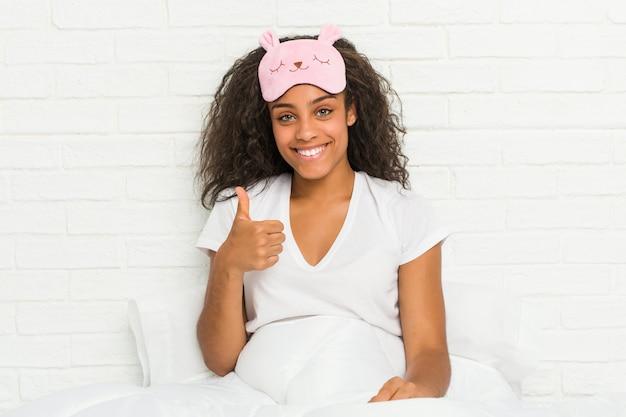 Junge afroamerikanerfrau, die auf dem bett trägt eine schlafmaske lächelt und daumen anhebt sitzt
