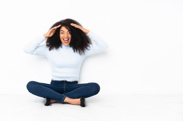 Junge afroamerikanerfrau, die auf dem boden mit überraschtem ausdruck sitzt