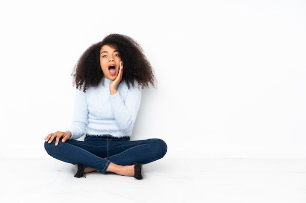 Junge afroamerikanerfrau, die auf dem boden mit überraschung und schockiertem gesichtsausdruck sitzt