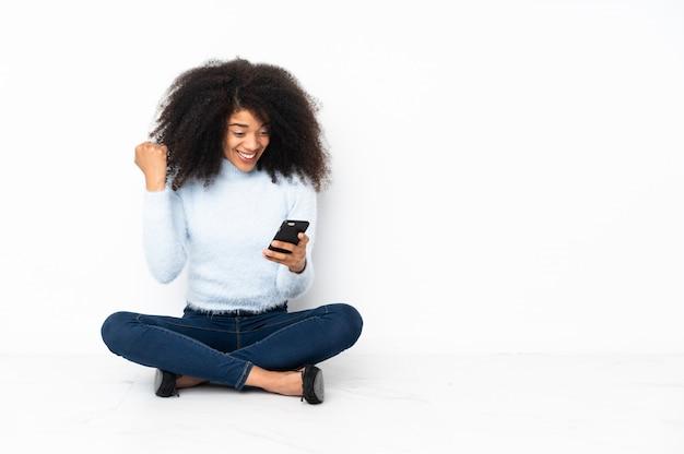 Junge afroamerikanerfrau, die auf dem boden sitzt, überrascht und eine nachricht sendend