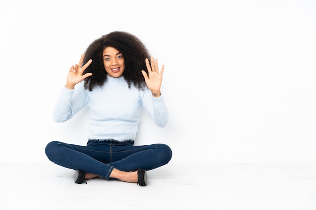 Junge afroamerikanerfrau, die auf dem boden sitzt und acht mit den fingern zählt