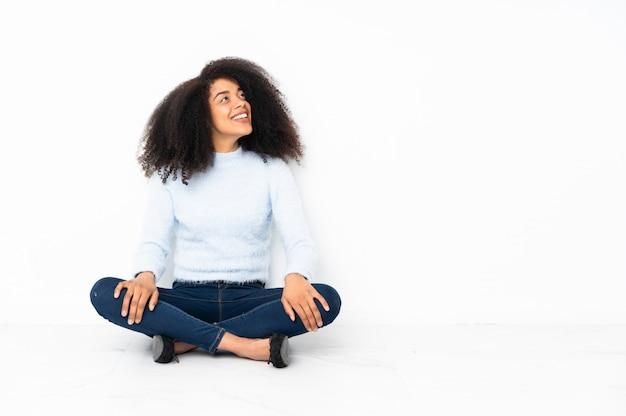 Junge afroamerikanerfrau, die auf dem boden sitzt und beim lächeln nach oben schaut