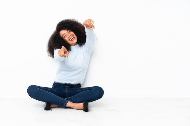 Junge afroamerikanerfrau, die auf dem boden sitzt, zeigt finger auf sie beim lächeln