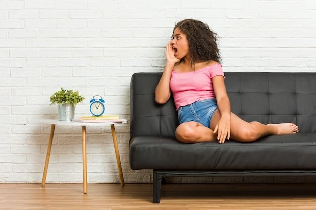 Junge afroamerikanerfrau, die auf dem sofa schreit und hält palme nahe geöffnetem mund sitzt.