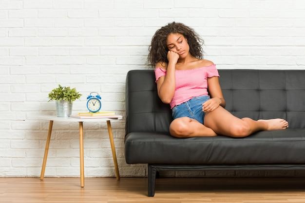 Junge afroamerikanerfrau, die auf dem sofa sitzt, das traurig und nachdenklich sich fühlt und kopienraum betrachtet.