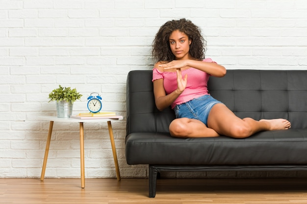 Junge afroamerikanerfrau, die auf dem sofa sitzt und eine auszeitgeste zeigt.