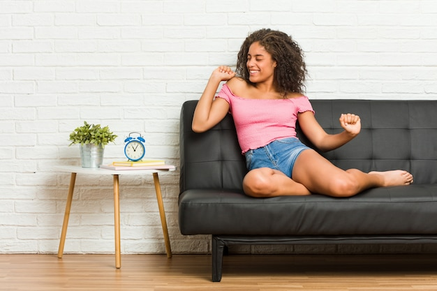 Junge afroamerikanerfrau, die auf dem sofatanzen sitzt und spaß hat.