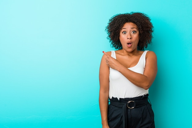 Junge afroamerikanerfrau, die auf die seite zeigt