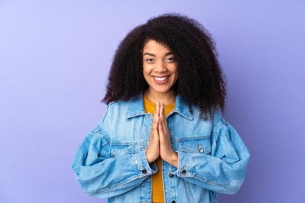 Junge afroamerikanerfrau, die auf lila isoliert wird, hält palme zusammen. person fragt nach etwas