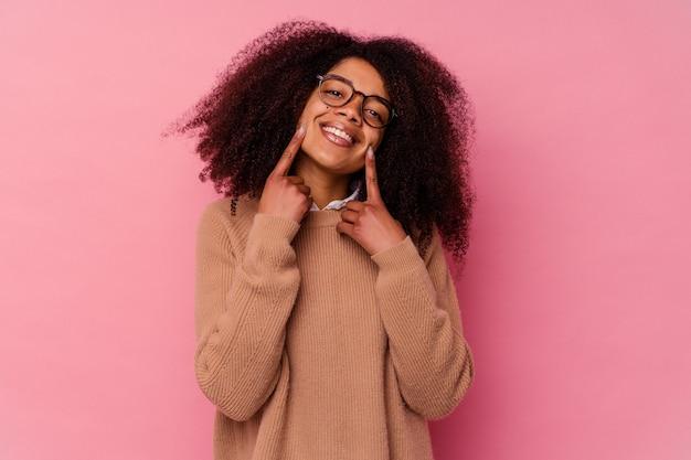 Junge afroamerikanerfrau, die auf rosa wandlächeln lokalisiert ist, zeigt finger auf mund.