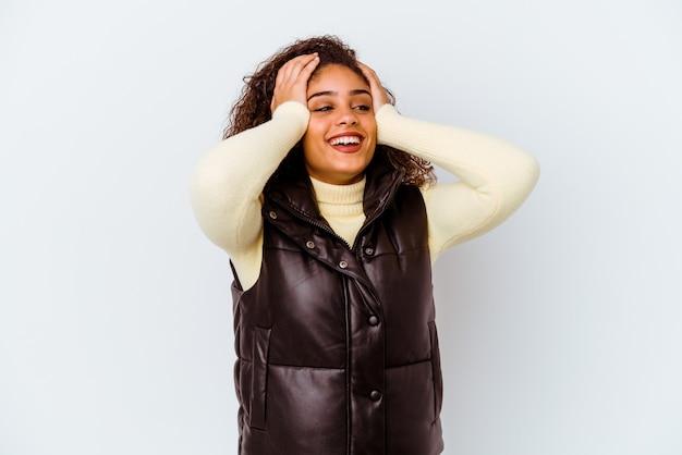 Junge afroamerikanerfrau, die auf weißem hintergrund lokalisiert wird, lacht freudig und hält die hände auf dem kopf. glück-konzept.