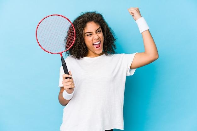 Junge afroamerikanerfrau, die badminton spielt
